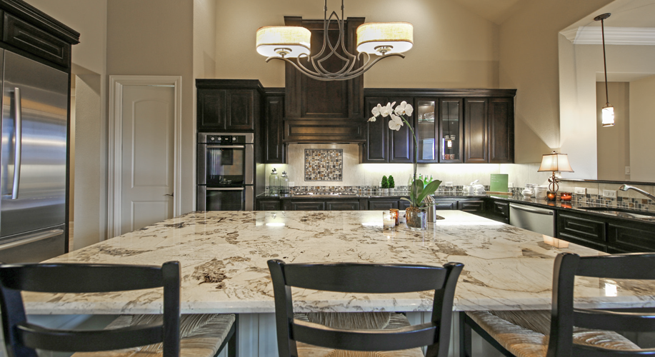 Open To The Living Room, This Kitchen Exudes Warmth With Its Dark Cabinets  That Contrast Elegantly With The Light Countertops And Backsplash.
